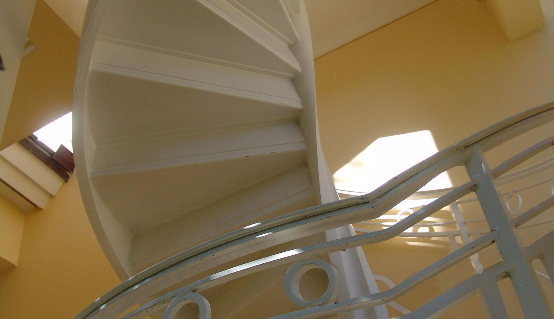 cropped photo of a residential iron spiral staircase